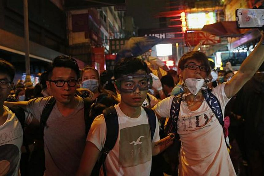 A pro-democracy protester takes a photo of the police (not in picture) near other protesters during a confrontation with the police at Mongkok shopping district in Hong Kong early Nov 29, 2014. -- PHOTO: REUTERS
