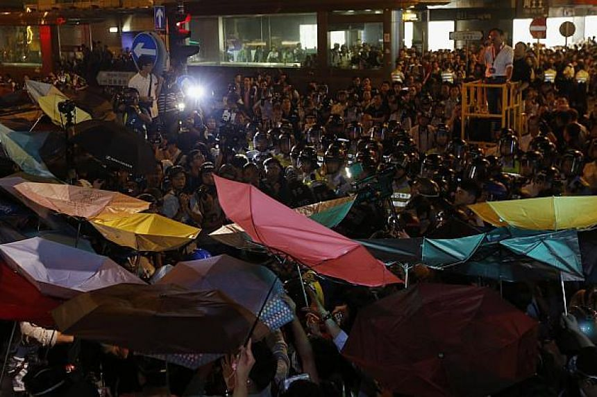 Pro-democracy protesters carrying umbrellas confront riot police at Mongkok shopping district in Hong Kong early Nov 29, 2014. -- PHOTO: REUTERS