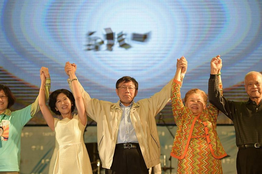 Newly elected independent Taipei Mayor Ko Wen-je (centre) joining hands with his relatives after winning the Taipei Mayoral elections in Taipei on Nov 29, 2014. Taiwan's premier resigned after his Beijing-friendly ruling party suffered a landslide de