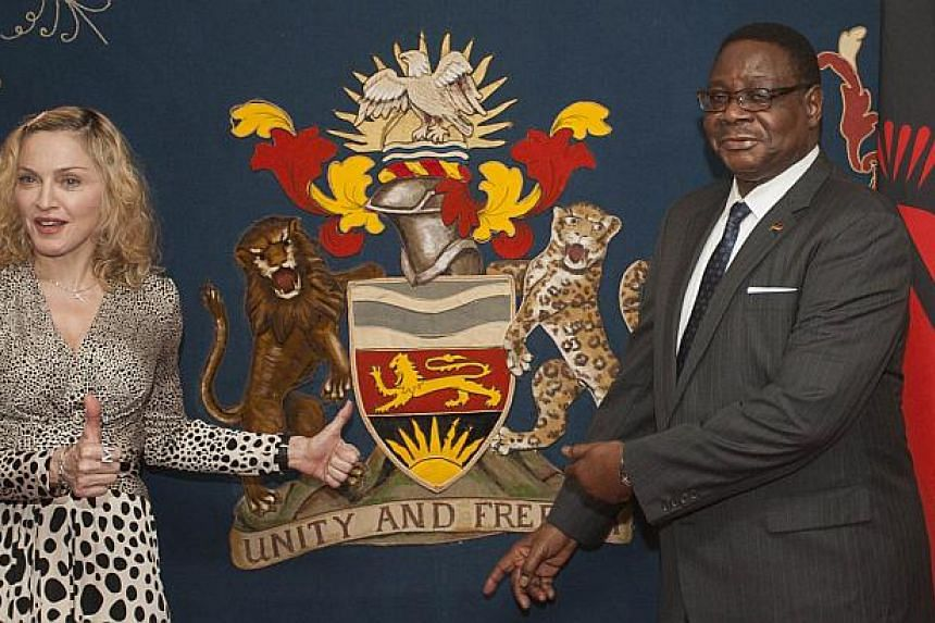 US pop star Madonna poses with Malawi's president Peter Mutharika prior to their meeting at Kamuzu Palace in the Capital Lilongwe, on Nov 28, 2014.Madonna met Malawi's new president on Friday after her VIP status was restored in the country whe