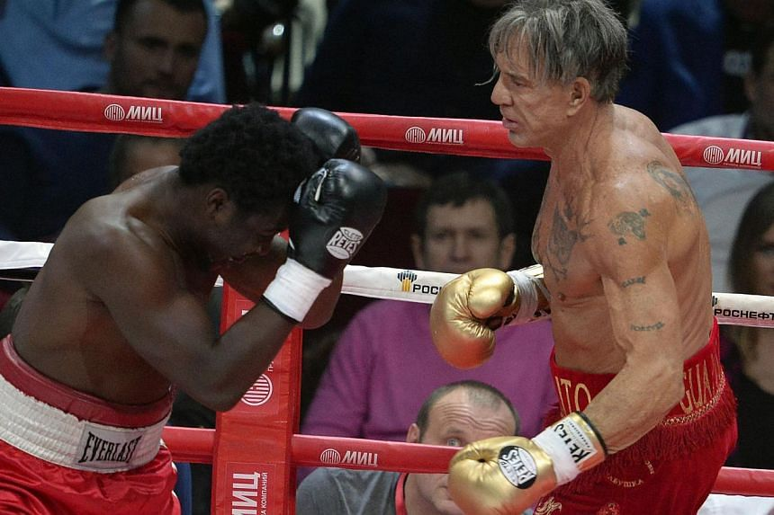 Hollywood actor Mickey Rourke (right), 62, fights with US professional Elliot Seymour, 29, in Moscow on Nov 28, 2014.Rourke beat his far younger opponent in the second round.-- PHOTO: AFP