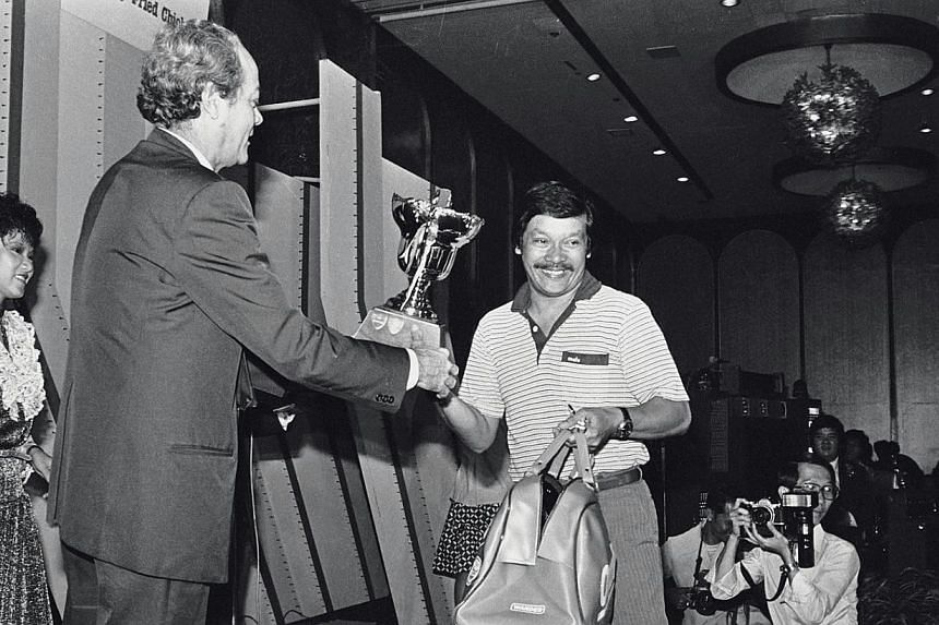 Ahmad Wartam, on behalf of his son Fandi Ahmad, receives theFootballer of the Year trophy at the annual Soccer Ball from then Law Minister E W Barker in 1982. -- PHOTO: ST FILE