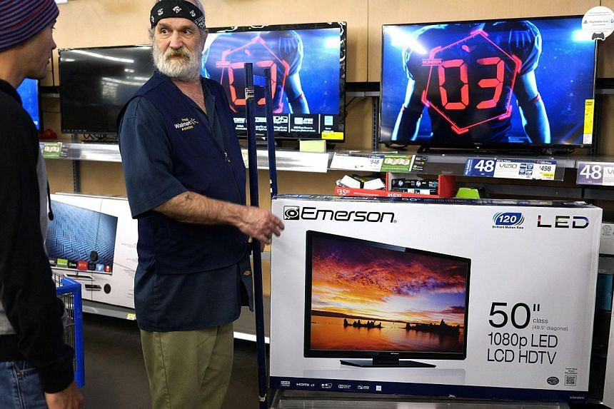 """A Walmart employee shows a customer (left) a 50-inch TV on sale for US$218 (S$284) on Black Friday in Broomfield, Colorado Nov 28, 2014. Black Friday, the biggest US shopping """"holiday"""", kicked off with expectations that lower fuel prices and higher c"""