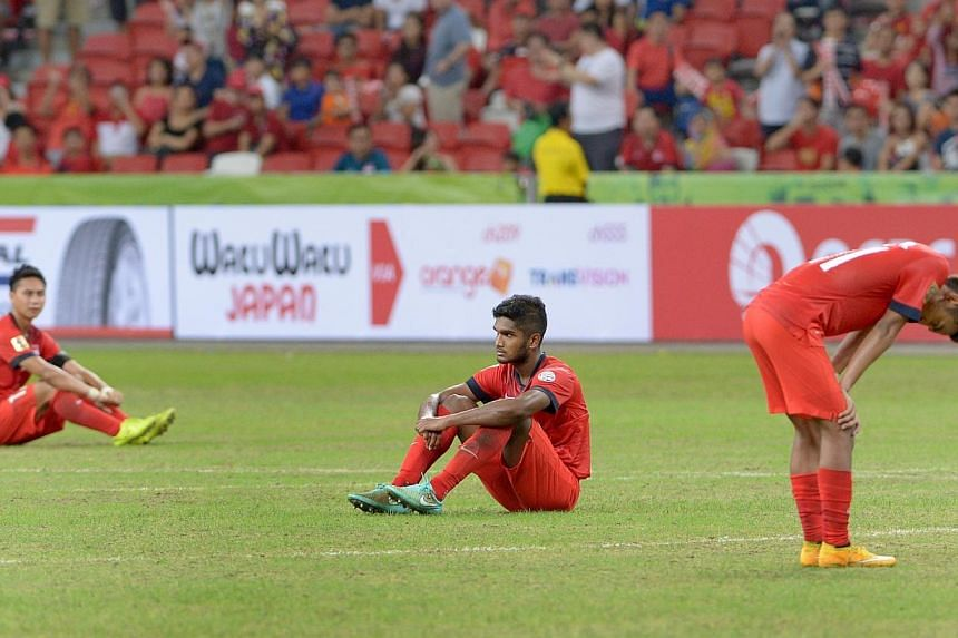Dejected Singapore players (from left)Shahril Ishak, Hariss Harun and Faris Ramli on the pitch after their 3-1 loss to bitter rivals Malaysia in their AFF Suzuki Cup match at the National Stadium on Nov 29, 2014. -- ST PHOTO: LIM SIN THAI
