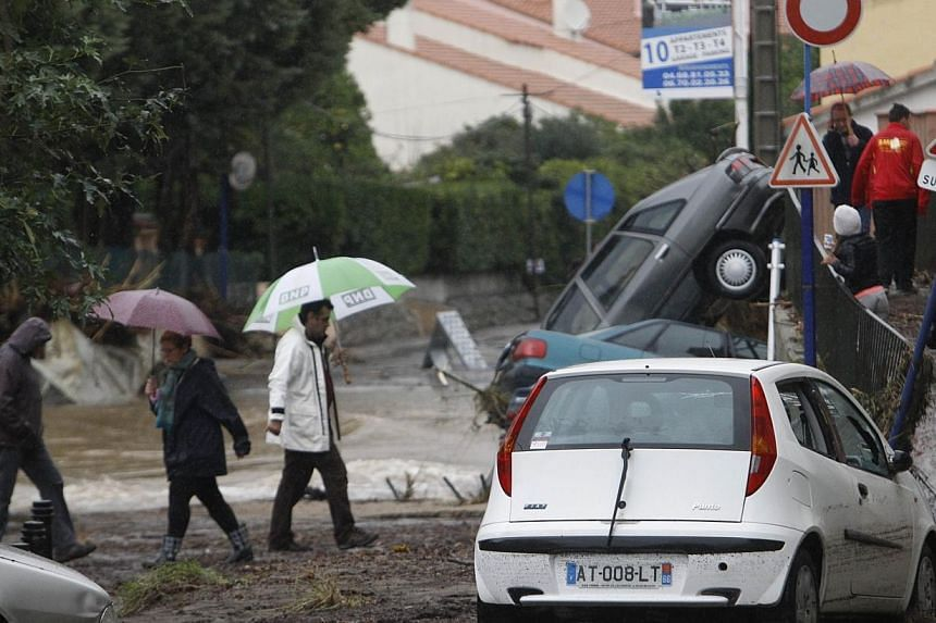 People walk in mud-covered streets near damaged cars after the river Massane flooded the city of Argeles-sur-Mer, southern France, due to heavy rains on Nov 30, 2014. -- PHOTO: AFP