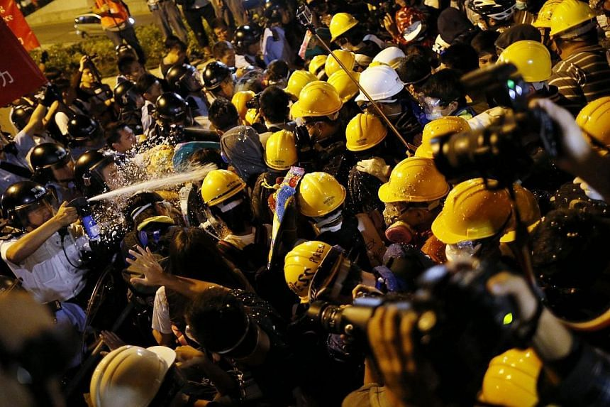 Police use pepper spray during clashes with pro-democracy protesters close to the government headquartersin Hong Kong, on Nov 30, 2014. -- PHOTO: REUTERS