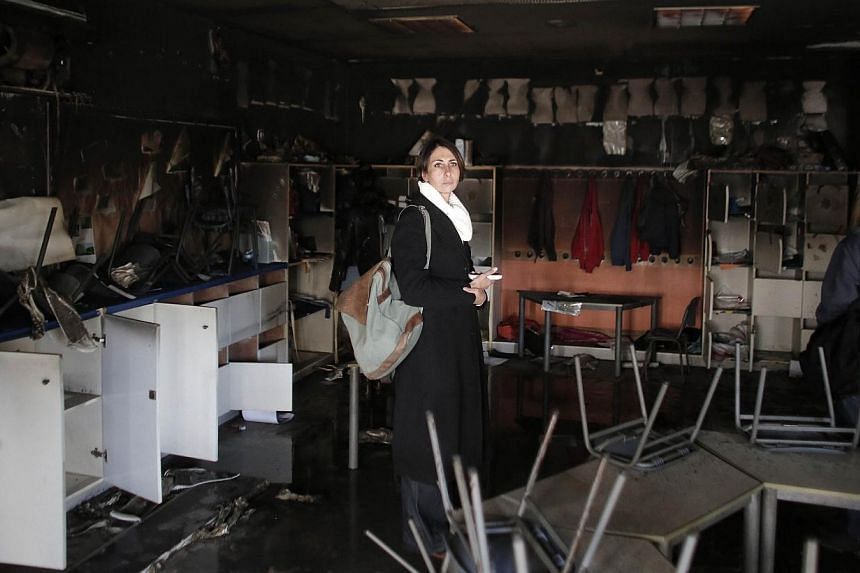 A woman inspects the damage on the aftermath of an arson attack that targeted first-grade classrooms at a Jewish-Arab school near the Arab neighborhood of Beit Safafa, in southern Jerusalem, on Nov 30, 2014.The attack sparked a wave of condemna