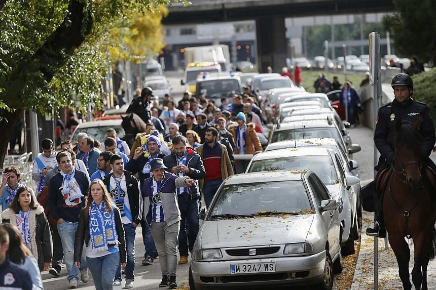 Spanish police escort Deportivo Coruna fans upon leaving Vicente Calderon stadium after their Spanish first division soccer match against Atletico Madrid in Madrid, on Nov 30, 2014. -- PHOTO: REUTERS