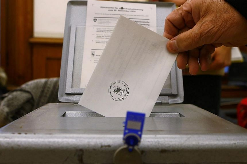 A man casts his voting ballot at the polling station in the Spitalacker school in Bern on Nov 29, 2014.The Swiss voted early on Sunday in three national referendums, including one calling for dramatic immigration cuts in the name of saving the