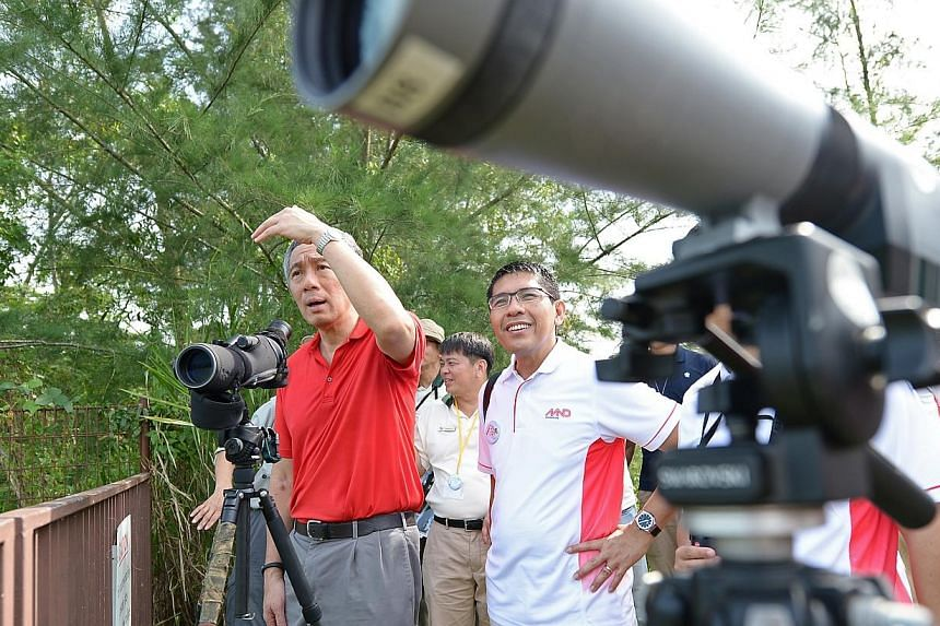 Dr Mohamad Maliki Bin Osman (right), Minister of State, Ministry of National Development & Ministry of Defence, checking out wild birds at Ketam Quarry in Pulau Ubin. -- ST PHOTO: NG SOR LUAN