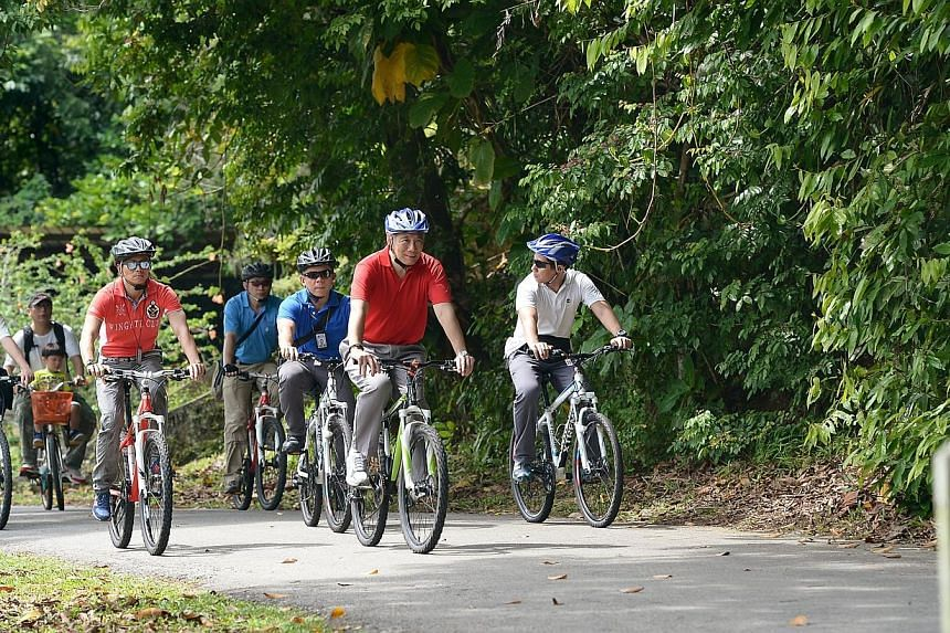 PM Lee taking a 4km bike ride in Pulau Ubin on Ubin Day. PM Lee is the guest of honour at this year's Ubin Day, the first in over a decade.-- ST PHOTO: NG SOR LUAN