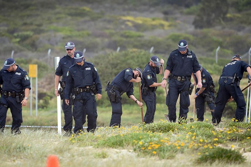 Police search the sand dunes after children playing at a Sydney beach on Nov 30, 2014, stumbled across the body of a baby buried under the sand. -- PHOTO: AFP