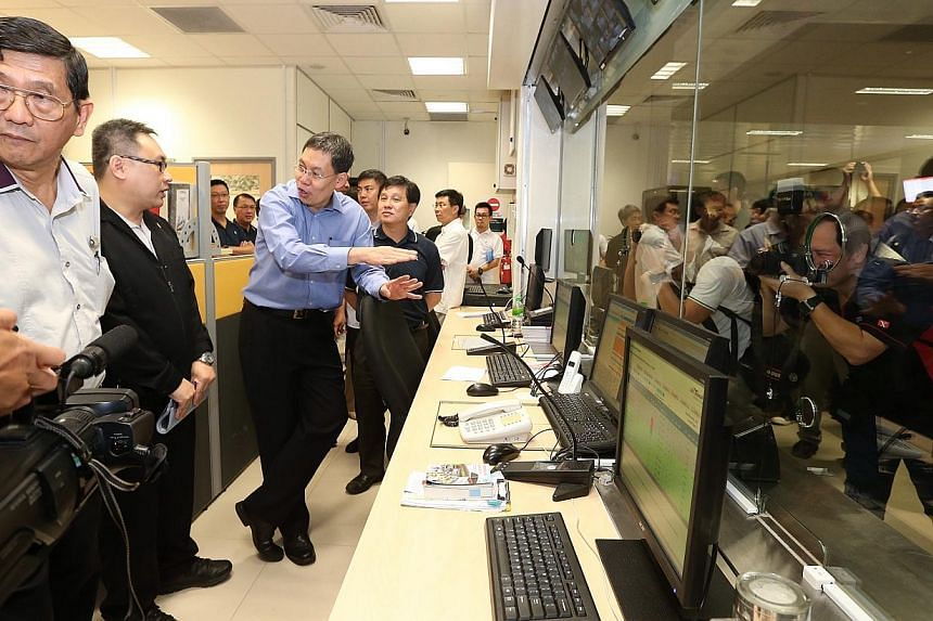 Minister for Transport Lui Tuck Yew (in blue) visits the passenger service office during a tour of the new Bedok Integrated Transport Hub.-- ST PHOTO: NEO XIAOBIN