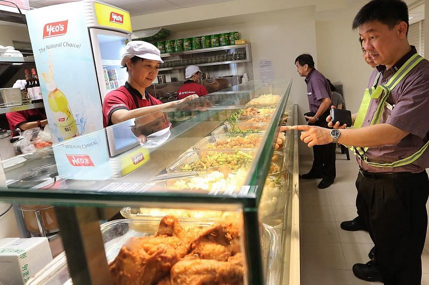 Senior bus captain Lee Chong Wah (extreme right), 45, gets lunch at the NTWU Canteen in the new Bedok Integrated Transport Hub.-- ST PHOTO: NEO XIAOBIN