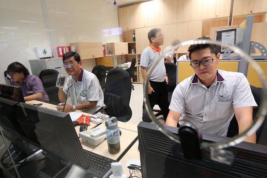 Assistant route master Chin Vui Min (extreme right), 30, seen working in the passenger service office at the new Bedok Integrated Transport Hub.-- ST PHOTO: NEO XIAOBIN