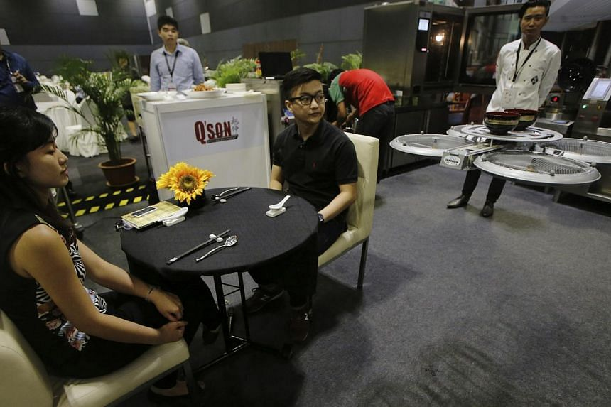 A flying robotic waiter served visitors (above) at the National Productivity Month exhibition in Singapore last month while a robot clears dishes at Supreme Tastes Jiang Nan Chun in Marina Square. -- PHOTO: REUTERS