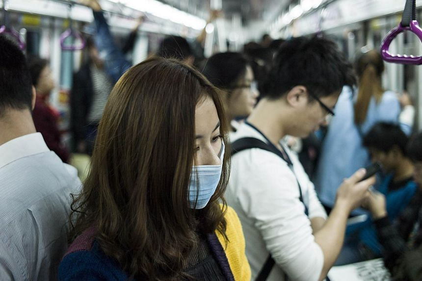 Forcing and cramming themselves onto the train in Beijing's overcrowded subway system has become a necessary daily ritual for the hundreds of thousands of workers commuting to the city.-- PHOTO: AFP