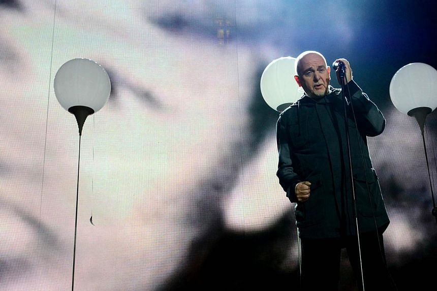 British singer Peter Gabriel performs during a Street Party organised by German governement to mark the 25th anniversary of the fall of the Berlin Wall, in front of the Brandenburg Gate on Nov 9, 2014 in Berlin. Musicians including Peter Gabriel and