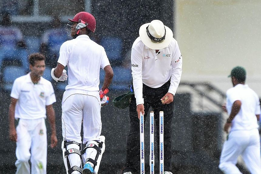 The umpire clears the wickets as players temporarily leave the field amid rain during a match between between the West Indies and Bangladesh on Sept 15, 2014. An umpire and former captain of Israel's national cricket team died on Saturday after being