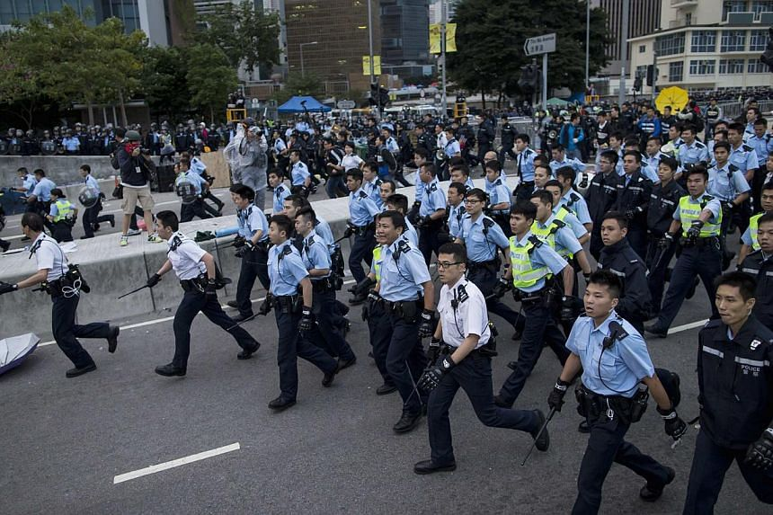 Police officers hold batons as they clear a demonstration site near the office of the Chief Executive in Hong Kong on Dec 1, 2014. -- PHOTO: REUTERS