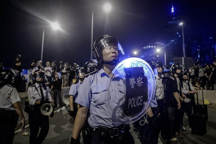 A policeman looks towards pro-democracy protesters outside the government headquarters in the Admiralty district of Hong Kong on Dec 1, 2014. -- PHOTO: AFP