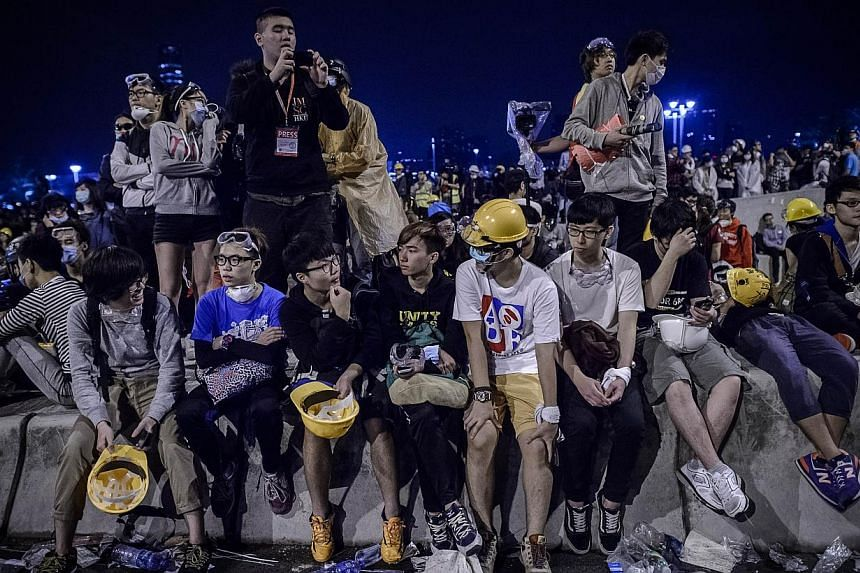 Pro-democracy protesters take a break in between clashes with police forces outside the government headquarters in the Admiralty district of Hong Kong on Dec 1, 2014. -- PHOTO: AFP