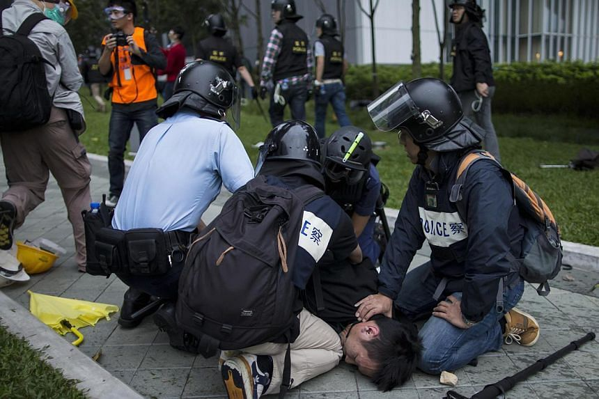 A pro-democracy protester is forced to the ground as police officers attempt to clear a demonstration site near the office of the Chief Executive in Hong Kong on Dec 1, 2014. -- PHOTO: REUTERS