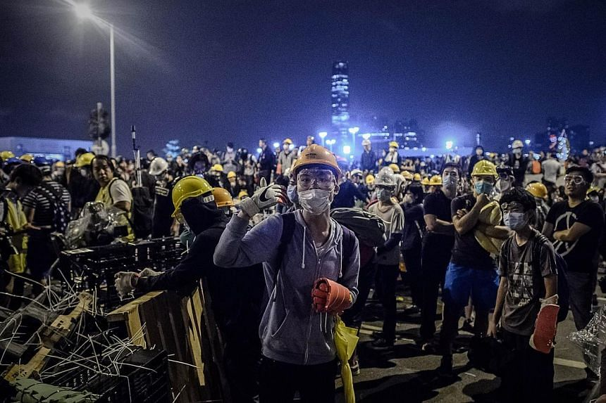Pro-democracy protesters gather as they set up a barricade (left) outside the government headquarters in the Admiralty district of Hong Kong on Dec 1, 2014. -- PHOTO:AFP