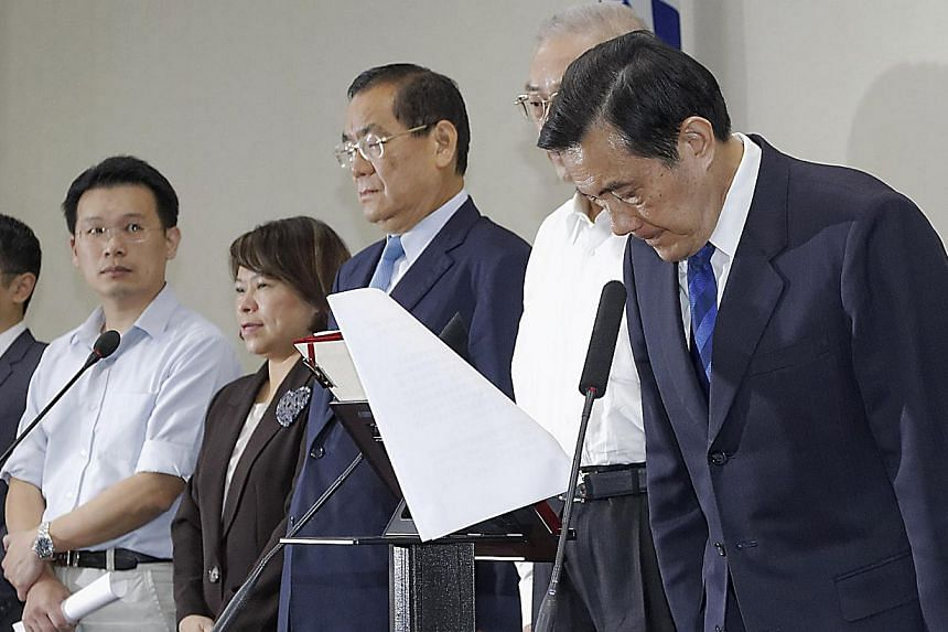 Taiwan President Ma Ying-jeou (right) bows during a news conference with party officials after the ruling Kuomintang (KMT) party was defeated in the local elections in Taipei on Nov 29, 2014. Taiwan's Cabinet will convene a meeting on Monday