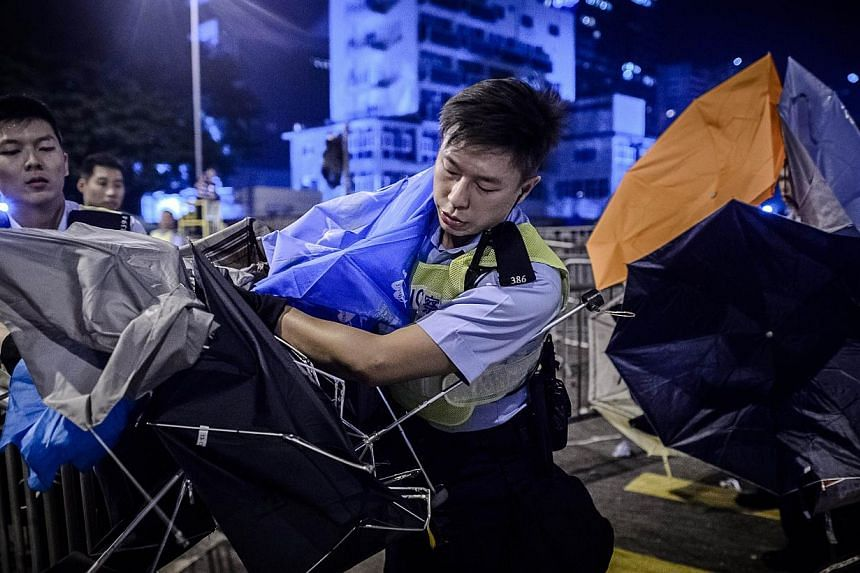 Policemen clear a road from umbrellas left behind during clashes with pro-democracy protesters outside the government headquarters in the Admiralty district of Hong Kong early Dec 1, 2014. -- PHOTO: AFP