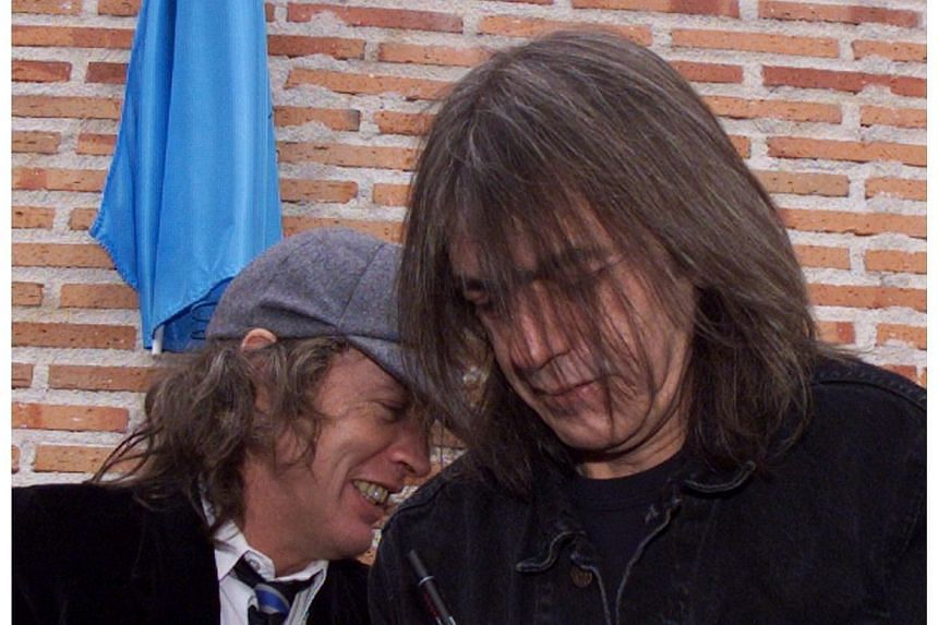 This file photo taken on March 22, 2000 shows Australian guitarists and brothers Angus (left) and Malcom Young (right) of the hard rock group AC/DC inaugurating a street named after them in Leganes, near Madrid in Spain. Angus Young said he first not