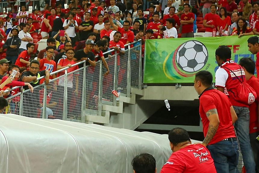 Singapore supporters hurling water bottles at the tunnel as the Malaysian players departed the pitch after their 3-1 AFF Suzuki Cup win over the Lions at the National Stadium on Nov 29, 2014. -- PHOTO: TNP