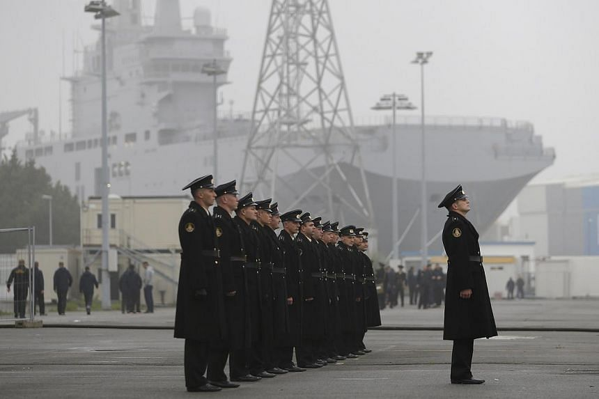 Russian sailors stand in formation in front of the Mistral-class helicopter carrier Vladivostok at the STX Les Chantiers de l'Atlantique shipyard site in Saint-Nazaire, western France, onNov 25, 2014. Russia said on Dec 1, 2014, that it would ca