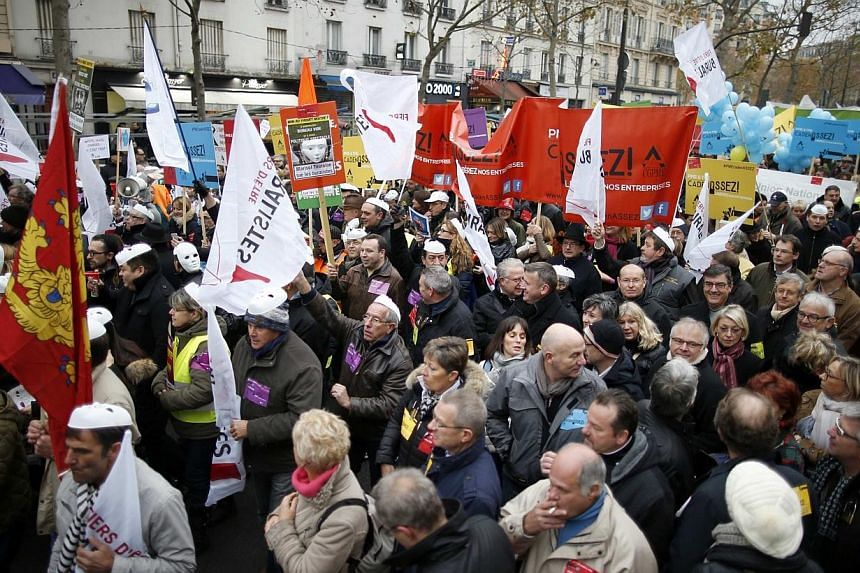 Heads of small and mid-size French companies hold banners as they attend a demonstration organized by the French CGPME (Confederation of Small and Medium Sized Enterprises) employers groups to protest against government policy and what they see as ex
