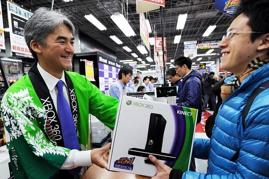 This file picture taken on Nov 20, 2010 shows Microsoft Japan Interactive Entertainment Business general manager Takashi Sensui (left) delivering the company's Xbox 360 Kinect to a Japanese customer (right) at a shop in the electronic goods district