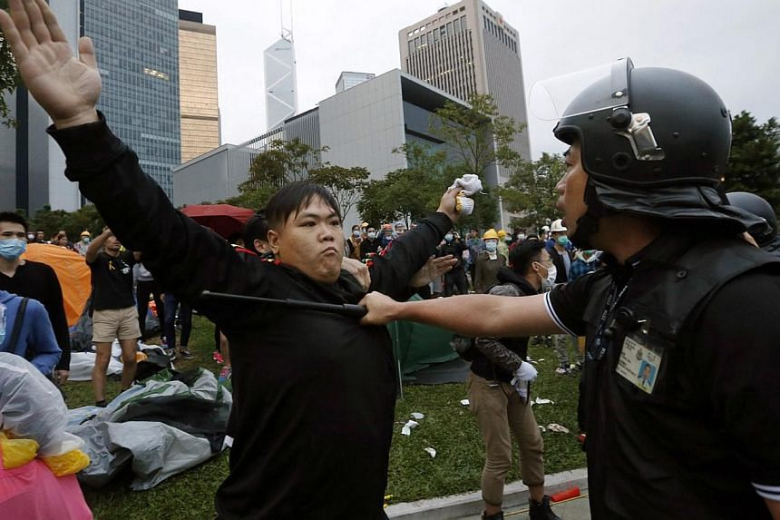 A pro-democracy protester blocks a riot policeman during a clash outside the government headquarters in Hong Kong Dec 1, 2014. Hong Kong police baton-charged and pepper-sprayed thousands of pro-democracy demonstrators in the early hours of Monday who