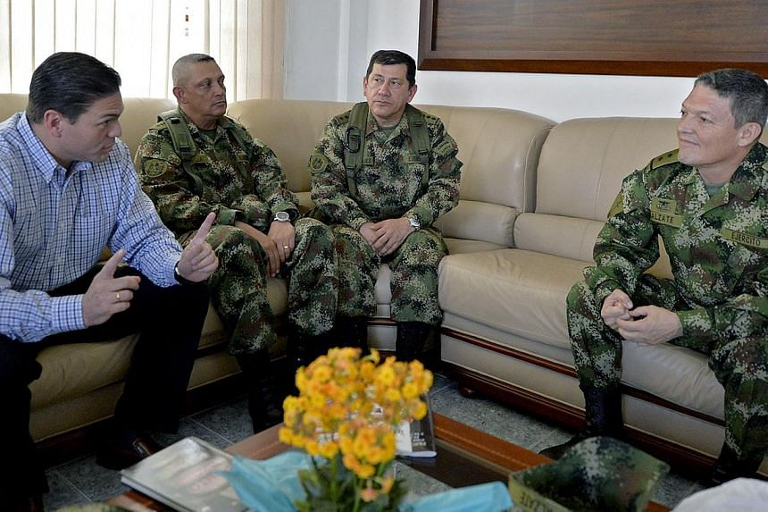 Colombian Defense Minister Juan Carlos Pinzon (left) talking with Army Force Commander Juan Pablo Rodriguez (second from right), Army Commander in Chief, General Jaime Alfonso Lasprilla (second from left), and released Brigadier General Ruben Alzate