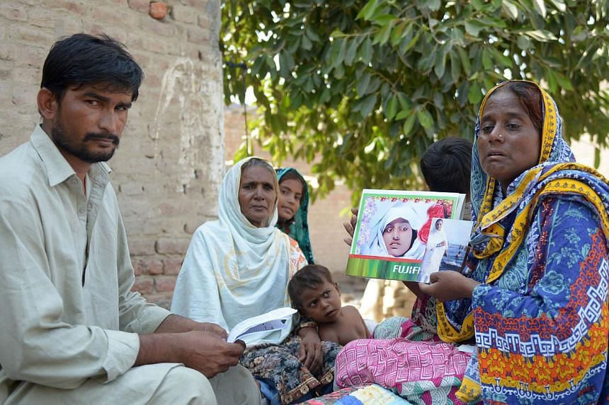 Villager Razia Shaikh holding up photos of her daughter, the victim of an honour killing, at an Agence France-Presse interview in Sukkur, Sindh province, on Oct 18. The family or community members who carry out such killings when a woman is declared