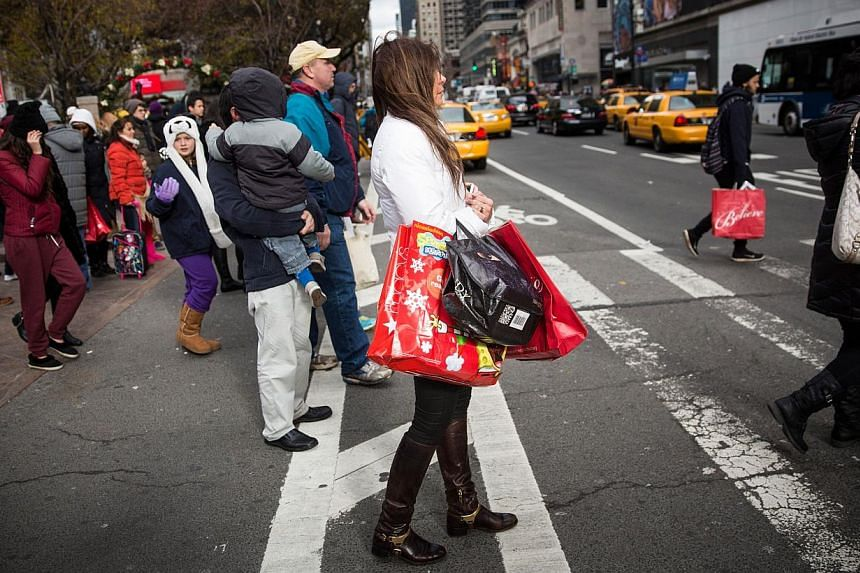Shoppers carry recent purchases through Herald Square on the morning of Nov 28, 2014 in New York City. Consumer spending during America's Thanksgiving weekend dropped compared to last year, but the decline can be attributed to an improving economy an