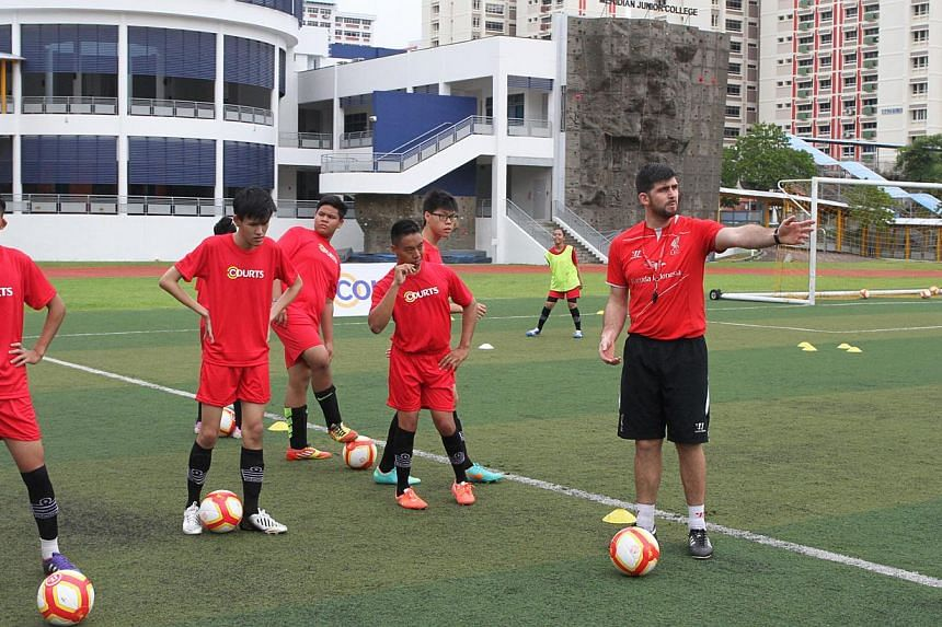 Anthony Owens (right), Coach for the Courts and Liverpool Football Academy 2014, and participants from the Sg Cerebral Palsy Football Team and Special Olympics Football Team. -- PHOTO: COURTS SINGAPORE