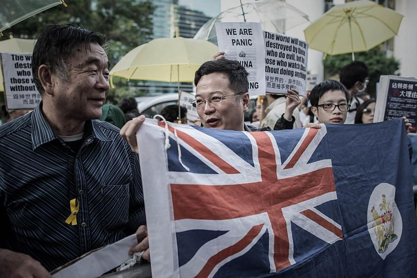 Pro-democracy protesters hold a Hong Kong colonial flag as they stage an occupy protest outside the British consulate in the Admiralty district of Hong Kong on Nov 21, 2014. -- PHOTO: AFP
