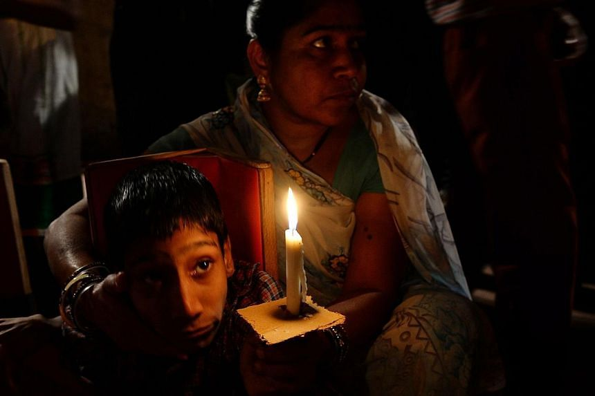 An Indian second-generation victim of the Bhopal gas disaster holds a candle during a vigil against the Union Carbide factory in Bhopal on Nov 30, 2014. -- PHOTO: AFP