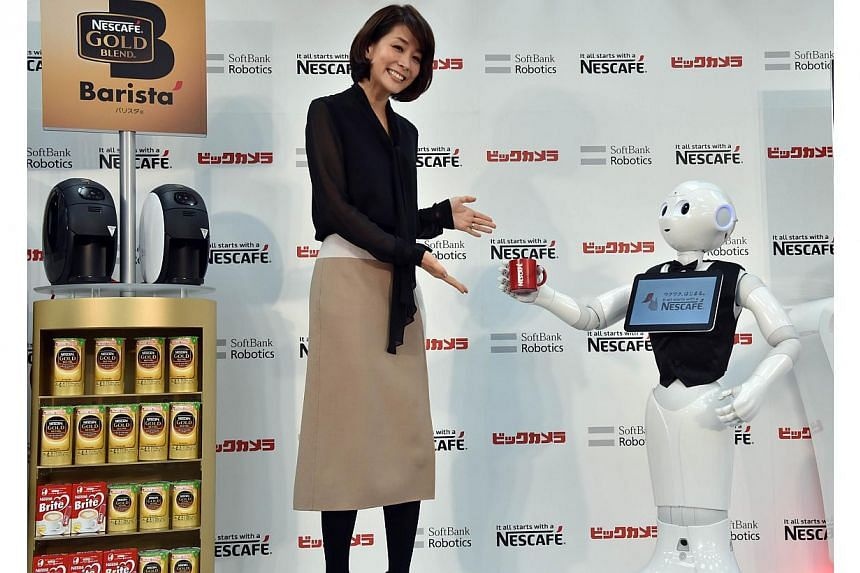 Japanese telecom giant Softbank's humanoid robot Pepper introduces Nestle's coffee machines at an electric shop in Tokyo on Dec 1, 2014. -- PHOTO: AFP