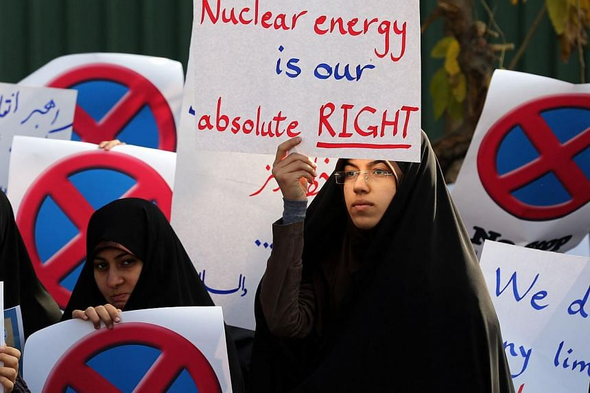 "An Iranian student holds a placard reading ""Nuclear energy is our absolute right"" during a demonstration outside the Teheran Research Reactor in the capital Teheran on Nov 23, 2014, to show support to Iran's nuclear programme. -- PHOTO: AFP"