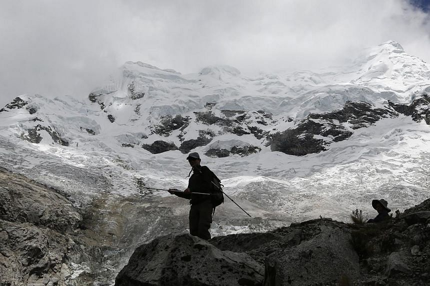 People walk near the Hualcan glacier in the Huascaran natural reserve in Ancash Nov 29, 2014. Peru will host the annual United Nation's Climate Change Conference (COP20), of the U.N. Framework Convention on Climate Change (UNFCCC) in Lima from Dec 1-
