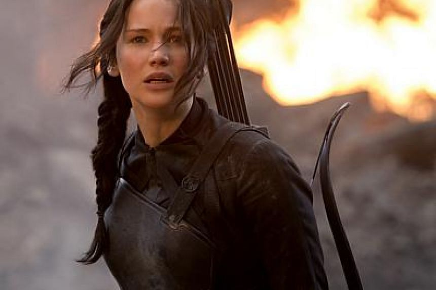 Jennifer Lawrence stars as reluctant rebel Katniss Everdeen in The Hunger Games: Mockingjay Part 1, which continues to fight off challengers such as the Penguins of Madagascar and Big Hero 6 to top the North American box office. -- PHOTO: CATHAY-KERI
