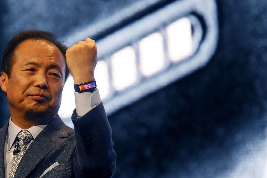 JK Shin, president and Head of IT and Mobile Communication Division of Samsung Electronics, shows off company's new Gear Fit fitness band during its launching ceremony at the Mobile World Congress in Barcelona. -- PHOTO: REUTERS