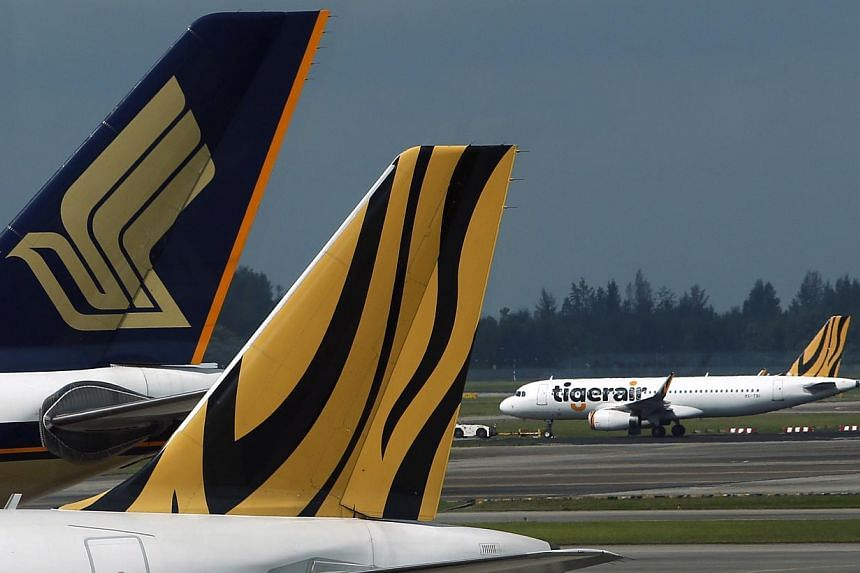 A Tiger Airways plane is towed on the runway past Singapore Airlines and Tiger Airways planes sitting on the tarmac at Changi Airport in Singapore. -- PHOTO: REUTERS
