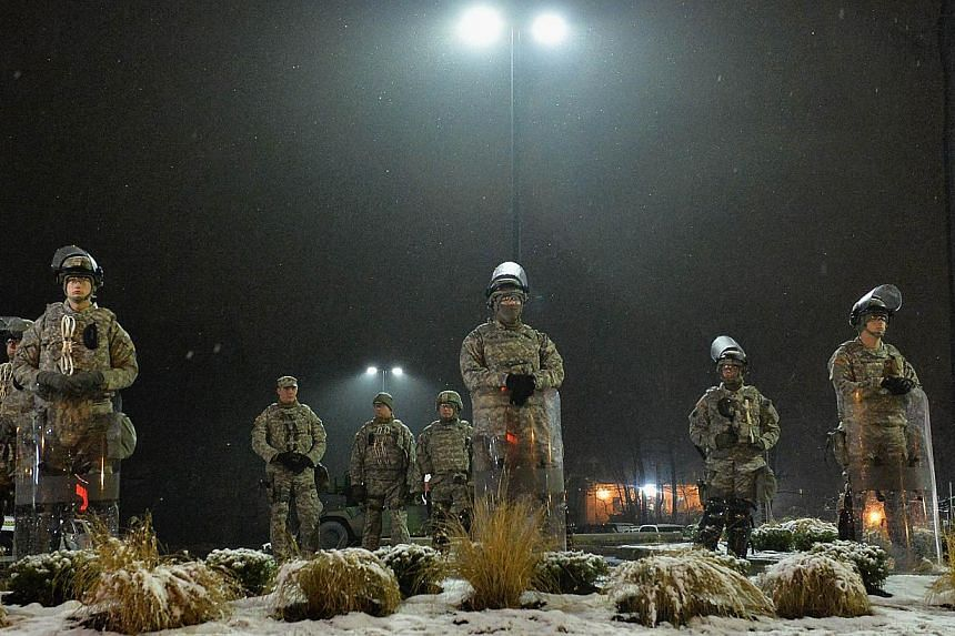 Members of the Missouri National Guard stand on patrol outside the Ferguson Police Department on Nov 26, 2014 in Ferguson, Missouri. -- PHOTO: AFP