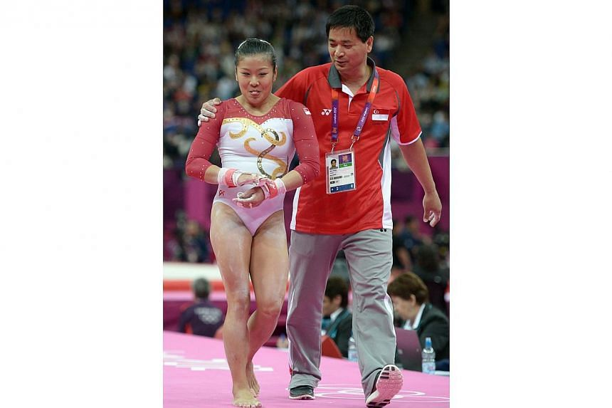 Singapore's gymnast Lim Heem Wei getting a pat from coach Zhao Qun for a job well done after her last event, the uneven bars, at the London Olympics on July 29, 2012. -- PHOTO: ST FILE